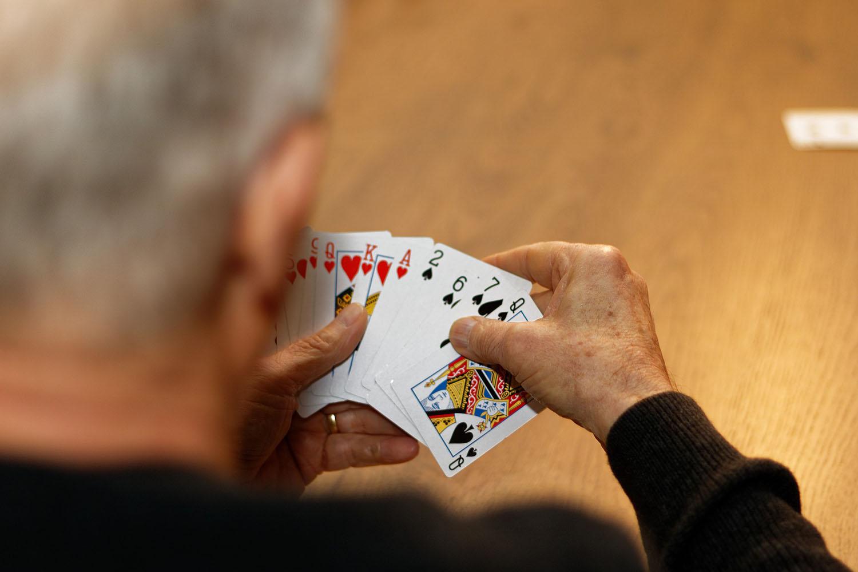 Ein älterer Mann mit Spielkarten in der Hand